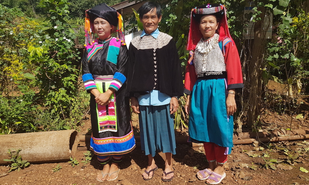 Three people in traditional dress Lisu Hill tribe
