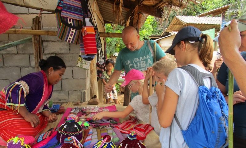 parents and children shopping in a village
