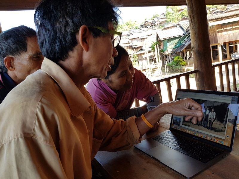 Villagers in the Lawa village Ban Dong looking at pictures made by Charles Keyes 50 years ago
