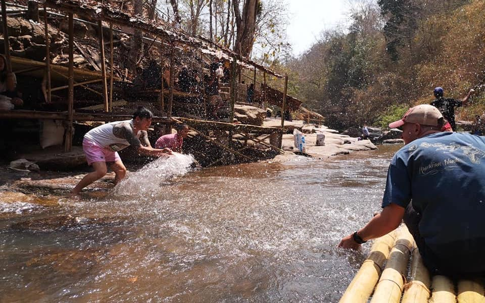 Locals and guests making fun during bamboo rafting