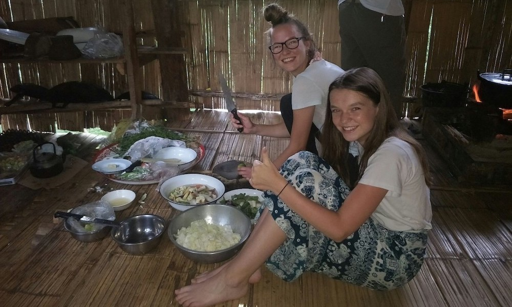 Two ladies helping cooking in a hut