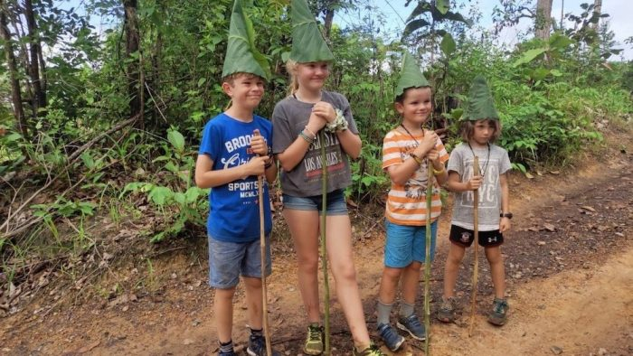 Four kids trekking with banana leaf hats family adventure