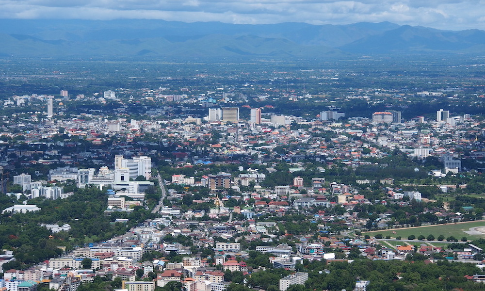 aerial view of city with skyscrapers and mountains