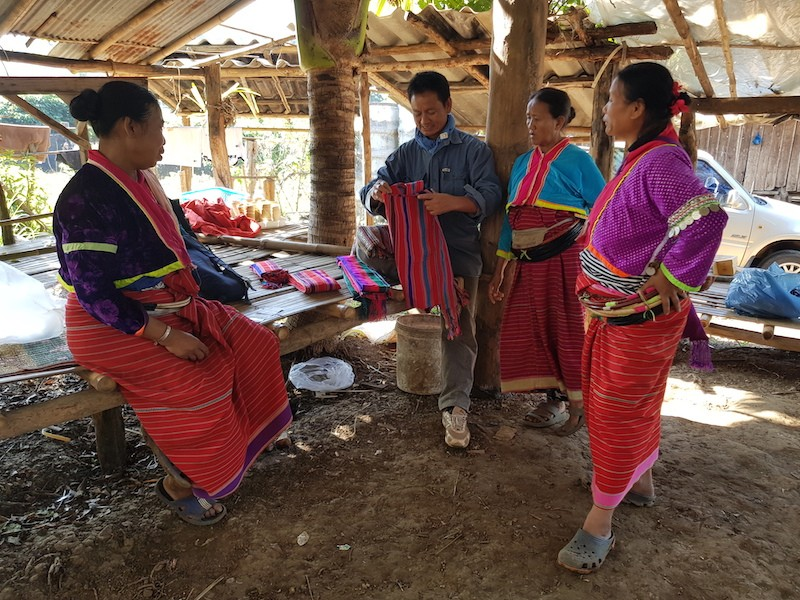 Three women in traditional dress and one man