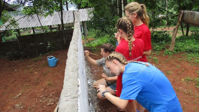 Female students painting on a wall community immersion