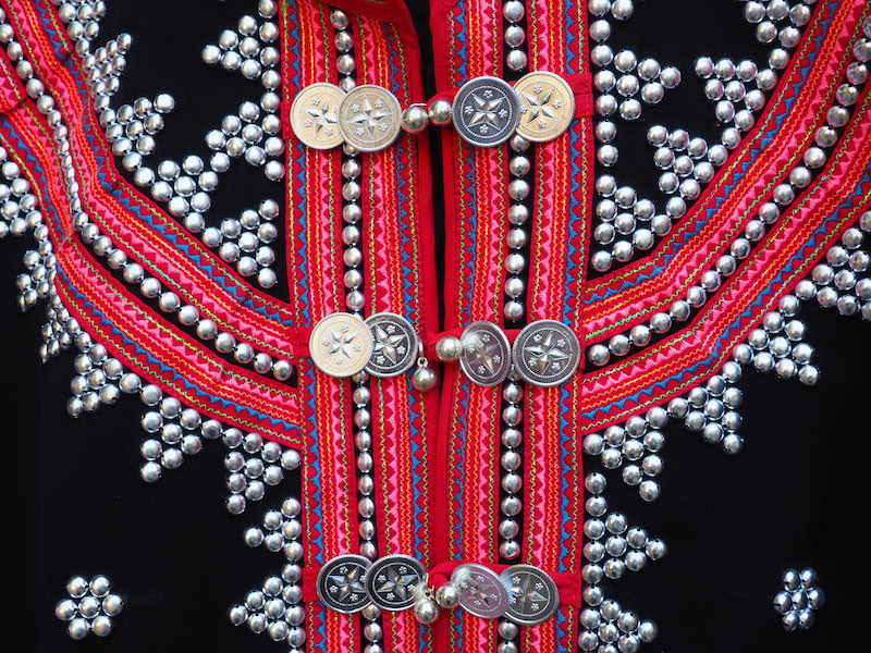 Silver jewellery on tribal jacket Lahu hill tribe