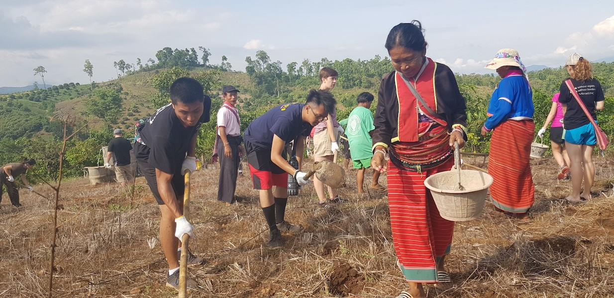 Tribal people and students working in the field