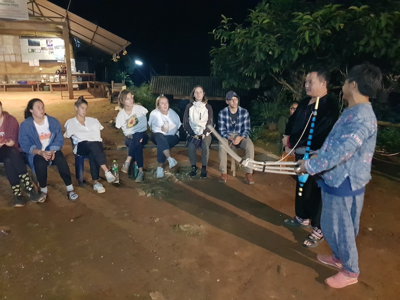 Tribal men demonstrating an instrument in the evening