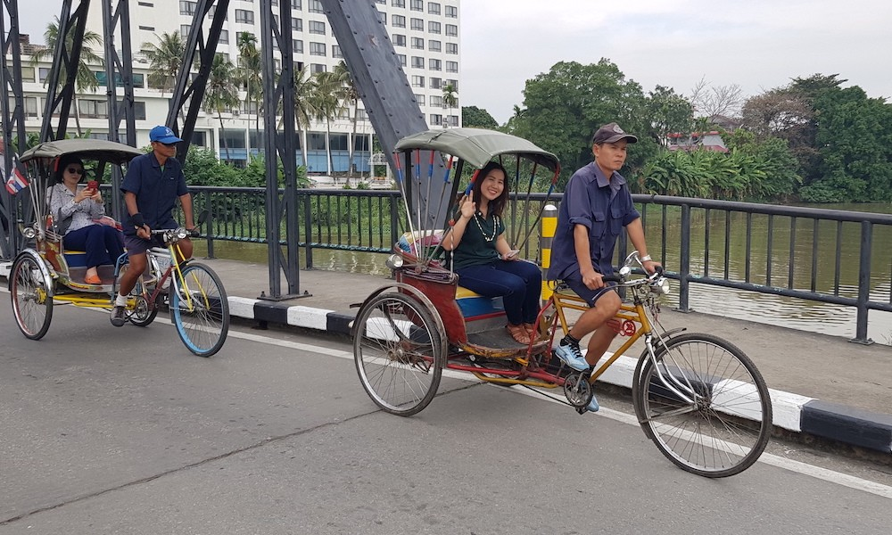 Samlors passing an iron bridge with tourists Chiang Mai on Three Wheels