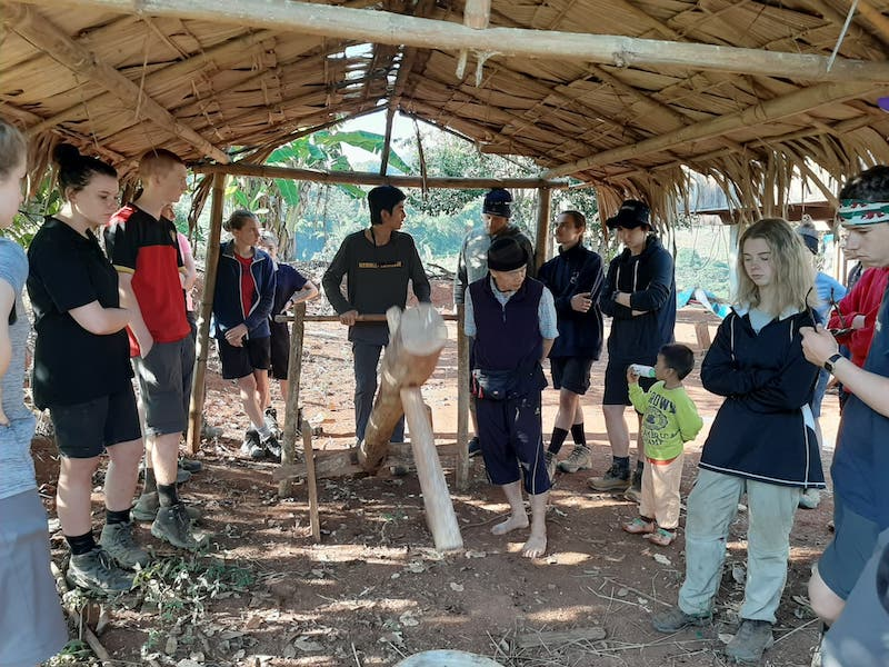 Students operating traditional rice pounder