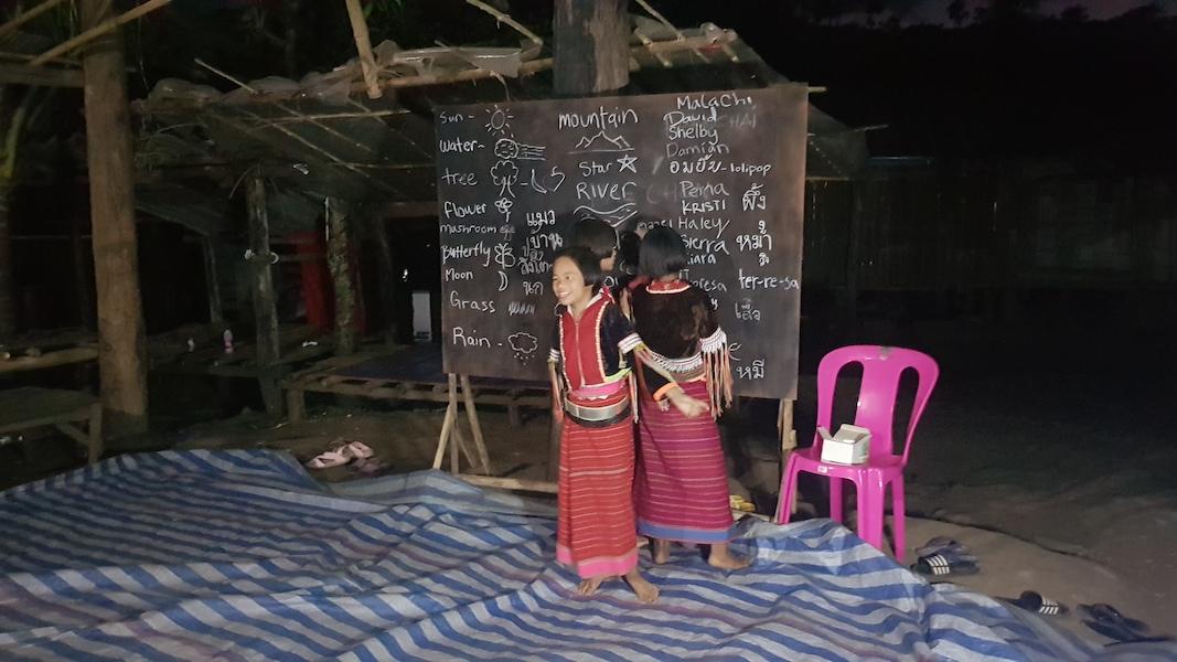 Kids in traditional dress in front of a blackboard