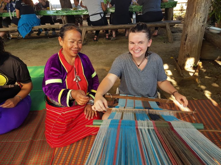 Girl weaving with local woman