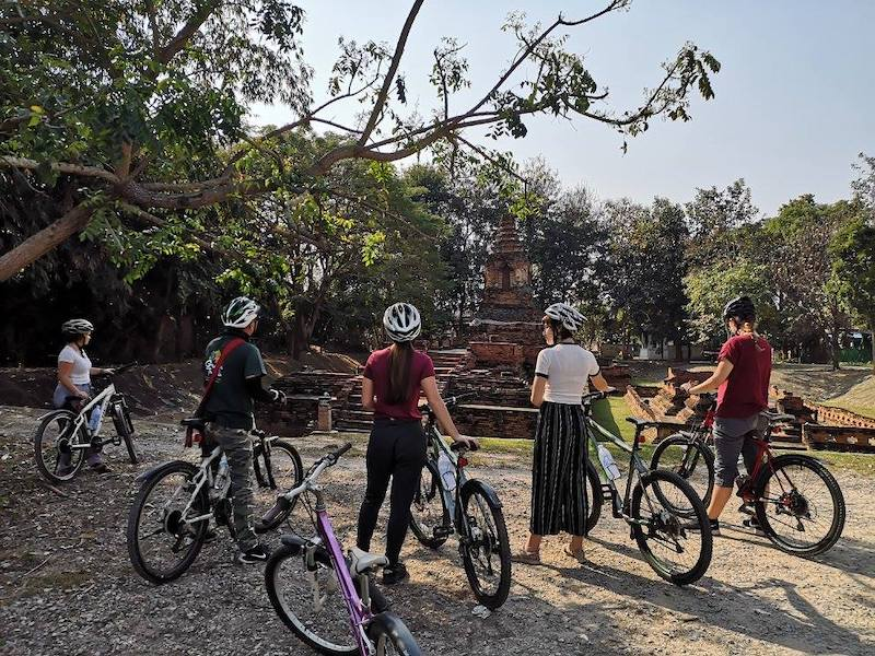 Five people on bicycles at ruins