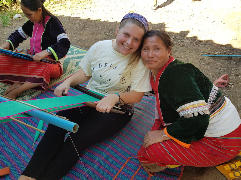 Student with tribal woman weaving