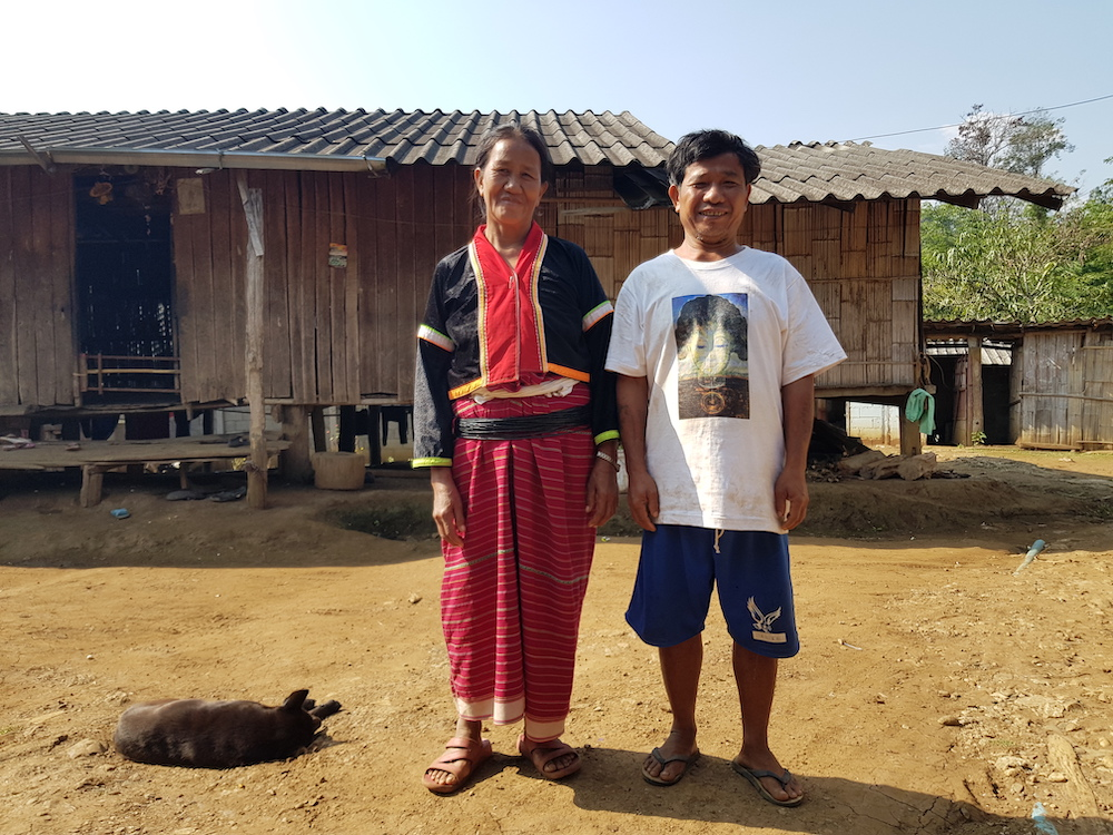 Man and woman in front of bamboo house