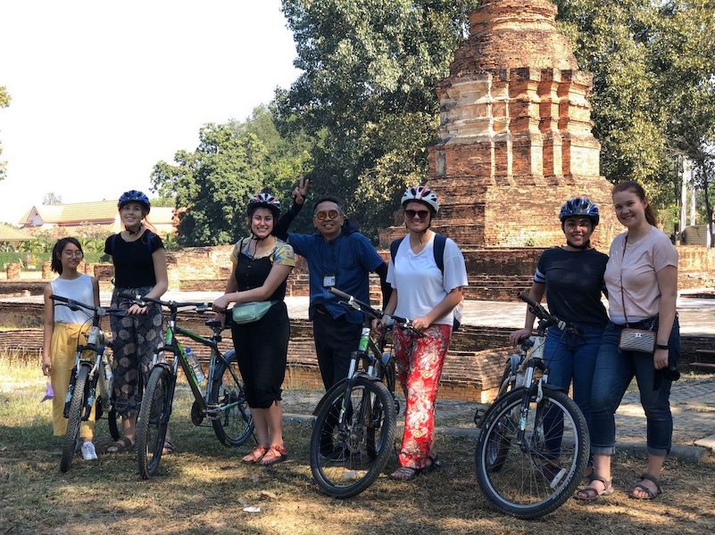 Cyclists in front of ruined chedi