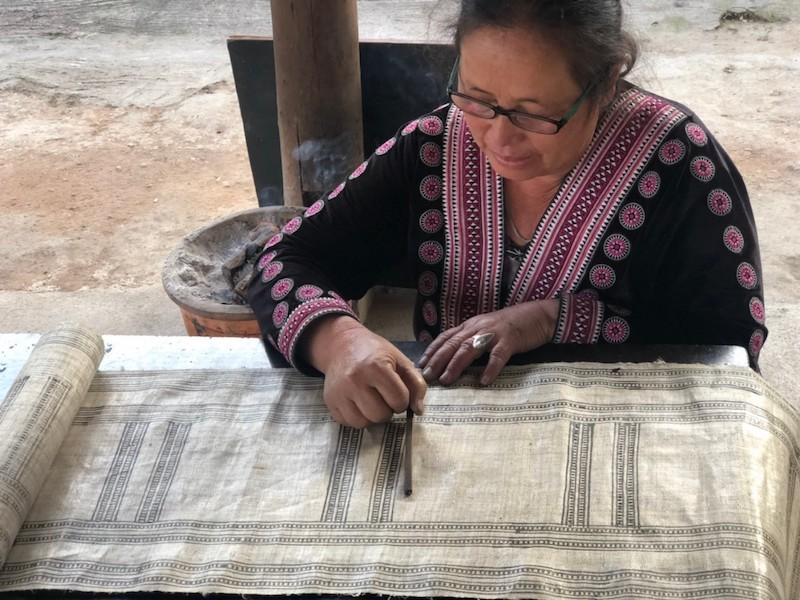 Tribal woman busy with batik