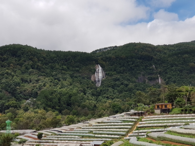 Waterfall on the mountain with greenhouses in front