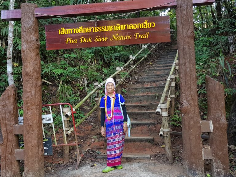 Tribal woman at nature trail sign Pha Dok Siew Trail