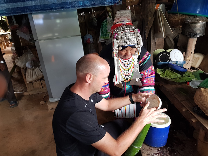 Tourist and tribal woman in kitchen